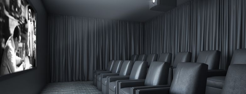 cinema room with comfortable chairs and big screen