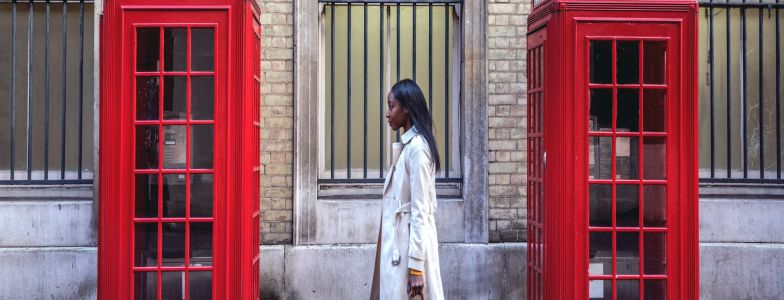 woman in trenchcoat walking down the street in london passing by two red phone booths